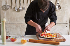 Restaurant hotel private chef preparing pizza adding toppings Stock Photos