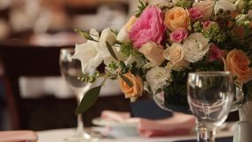 Restaurant interior decoration for wedding or birthday with white and blue colors. Holiday floristics or roses on tables stock footage