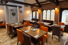Restaurant interior. Design with brown wooden tables, beige and orange chairs Stock Photography