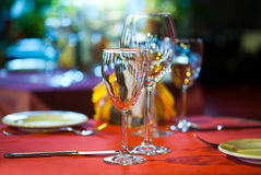 Restaurant interior: served table with a red tablecloth, red napkins, wine glasses and cutlery. Stock Photos