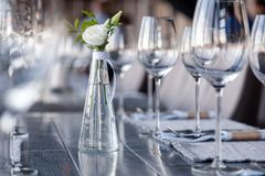 Transparent modern setting, glass vase with bouquet flowers on table in restaurant. Wine and water glasses stand on wooden table. Restaurant interior, serving royalty free stock photos