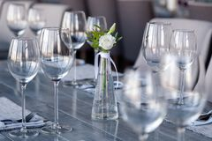 Transparent modern setting, glass vase with bouquet flowers on table in restaurant. Wine and water glasses stand on wooden table. Restaurant interior, serving stock image