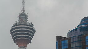 Restaurant in KL TV Tower through Clouds Motion. Closeup restaurant in upper part of Menara KL Tower and antennas through clouds motion skyscraper roof at stock video footage