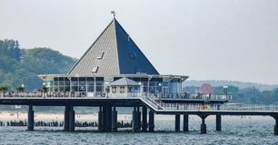 Restaurant located in pier in Heringsdorf in Germany. Piramid roof at the end of pier, which  is a stop for local cruise ship. Photo in 16:9 format. Photo Stock Photos