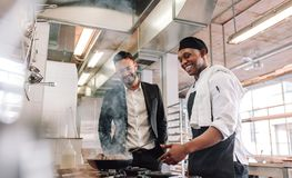Restaurant manager with chef cooking in kitchen. Smiling chef cooking food on stove with restaurant manager standing by. Restaurant manager with cook in Royalty Free Stock Photography