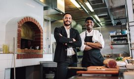 Restaurant manager with chef in kitchen. Portrait of restaurant manager with chef in kitchen. Businessman with professional cook standing together and looking at Royalty Free Stock Photography