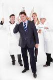 Restaurant manager with crazy staff behind. Angry restaurant staff attack a manager behind his back Royalty Free Stock Photography