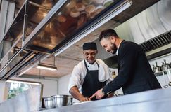 Restaurant manager with chef in kitchen. Restaurant manager discussing with chef in kitchen. Cook preparing a dish with restaurant owner standing by Stock Images