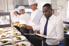 Restaurant manager with his kitchen staff. In the commercial kitchen Stock Image