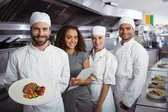 Restaurant manager with his kitchen staff. Portrait of restaurant manager with his kitchen staff in the commercial kitchen royalty free stock photos
