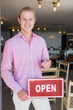 Restaurant manager holding open signboard. Portrait of restaurant manager holding open signboard in restaurant Stock Image