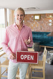Restaurant manager holding open signboard. Portrait of restaurant manager holding open signboard in restaurant Royalty Free Stock Photo