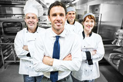 Restaurant manager posing in front of team of chefs Stock Photos
