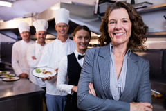 Restaurant manager posing in front of team of staff. Female restaurant manager standing in front of team of staff smiling at camera royalty free stock images
