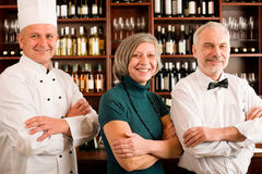 Restaurant manager posing with professional staff Stock Photo
