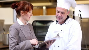 Restaurant manager speaking with head chef stock video