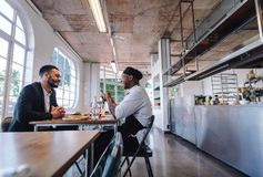 Restaurant manager talking with a professional chef. Cafe owner and cook sitting at a table and talking Royalty Free Stock Photography