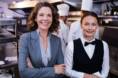 Restaurant manager and waitress smiling in commercial kitchen. Portrait of female restaurant manager and waitress smiling in commercial kitchen Stock Photography