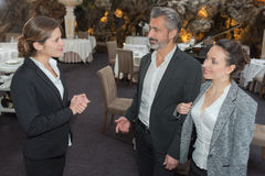 Restaurant manager welcomes couple in restaurant. Restaurant manager welcomes a couple in the restaurant Royalty Free Stock Photos