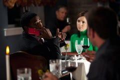 Restaurant: Mann stört andere, indem er Handy während der Mahlzeit verwendet Lizenzfreies Stockfoto