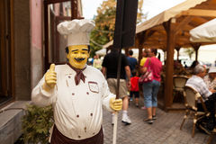 A restaurant mascot greeting customers. A cook's statue holding a sign at the entrance of a restaurant in Sibiu Royalty Free Stock Images