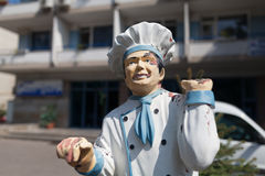 A restaurant mascot greeting customers. A shabby cook's statue holding a sign at the entrance of a restaurant in Constanta Stock Photo