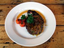 Restaurant meal of lamb steak and cherry tomatoes Royalty Free Stock Image