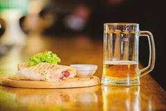 Restaurant meal traditional cuisine. Burrito tortilla served wooden board. Beer and food concept. Lavash burrito stuffed. Meat sausage and cheese sauce served stock photo