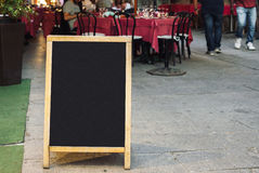 Restaurant menu blackboard. Blank restaurant menu blackboard with blurry people sitting at the table in the background Stock Photos