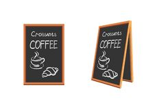 Restaurant menu eating and drinking on a black board with a wooden frame. A cup of coffee and a croissant. Isolated objec Royalty Free Stock Photography