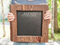 Restaurant menu on wooden board hold by man hand. Template mock Royalty Free Stock Photography