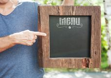 Restaurant menu on wooden board hold by man hand. Template mock Stock Photo