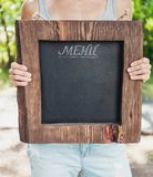 Restaurant menu on wooden board hold by woman hand. Template moc Royalty Free Stock Photography