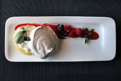 Restaurant meringue dessert with berries stock photography