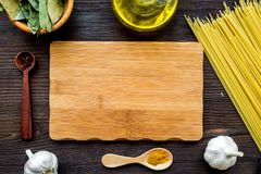 In restaurant. Mock up for menu or recipe. Wooden cutting board near ingredients. Raw pasta, oil, garlic, spices on dark royalty free stock images