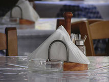 Restaurant. Napkin holder and empty ashtray are traditional tableware in every greek restaurant Royalty Free Stock Photos