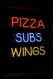 Restaurant Open. A neon sign with the words pizza, subs, and wings, on it advertising the type of fast food they sell royalty free stock image