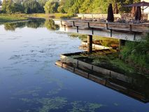 Restaurant open deck above water. Park restaurant open deck terrace above a pond with mirror like reflection Stock Image