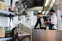 Restaurant owner with chef in kitchen. Cook talking with manager at cafe stock image