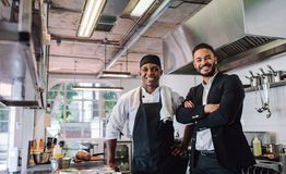 Restaurant owner with chef in kitchen. Portrait of restaurant owner with chef in kitchen. Businessman with professional cook standing together and looking at royalty free stock photo