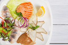 Restaurant plate of various fish with herbs, lemon and onion. Top view and white wooden table Royalty Free Stock Photo