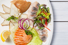 Restaurant plate of various fish with herbs, lemon and onion. Top view and white wooden table Royalty Free Stock Images