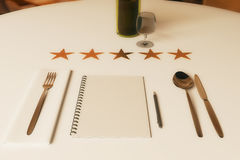 Restaurant rating concept. Close up of dining table with wine, cutlery, spiral notepad and five stars. 3D Rendering royalty free illustration
