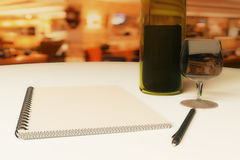 Restaurant rating and criticism concept. Close up of dining table with blank notepad, wine, cutlery and pen. Restaurant rating and criticism concept. 3D royalty free illustration
