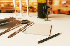 Restaurant rating and criticism concept. Close up of dining table with blank spiral notepad, candles, wine, cutlery and other items. Restaurant rating and royalty free illustration