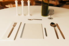 Restaurant rating and criticism concept. Close up of dining table with blank spiral notepad, wine, cutlery and other items. Restaurant rating and criticism royalty free illustration