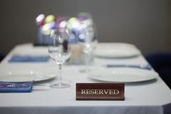 Restaurant reserved table sign with places setting and wine glasses ready for a party.  royalty free stock image