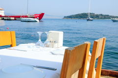 Restaurant by sea. A table by sea where boats and vessel Stock Photography