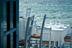 Restaurant on the sea. Restaurant tables on the sea in a Greek village Stock Image