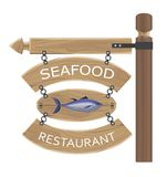 Restaurant Seafood Advertisement on Wooden Boards. Restaurant seafood advertisement with fish on wooden board attached by chain to horizontal notice and long Stock Photo